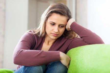 smutek dziewczyna siedzi na kanapie w domu Zdjęcie Seryjne