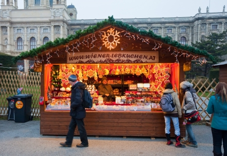 VIENNA, AUSTRIA - NOVEMBER 22: People walking at  Christmas Market at Maria-Theresien-Platz   in November 22, 2011 in Vienna, Austria.  Kiosk with cookies at Christmas market in Vienna