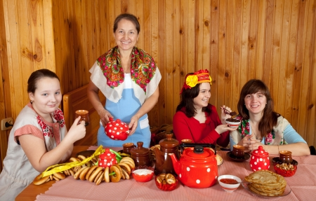 Women in traditional clothes drinks tea and eats pancake Stock Photo - 16620450