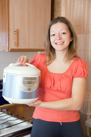 Smiling woman with  slow cooker in kitchen at home Stock Photo - 16620217