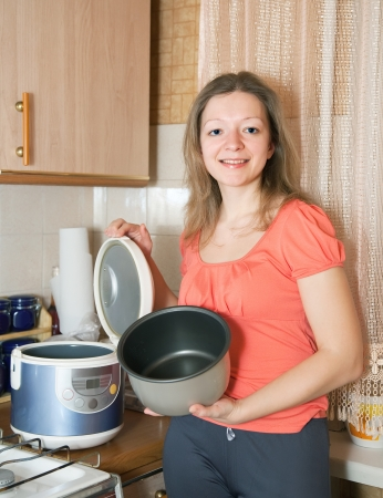 slow cooker: Woman with electric slow cooker in her kitchen Stock Photo