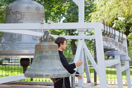 knell: YAROSLAVL, RUSSIA - JULY 28: Monk is rings the bell of Assumption cathedral in July 28, 2012 in Yaroslavl, Russia. Dormition Cathedral was built in 1215 and demolished in 1937. Now there is recovery Editorial