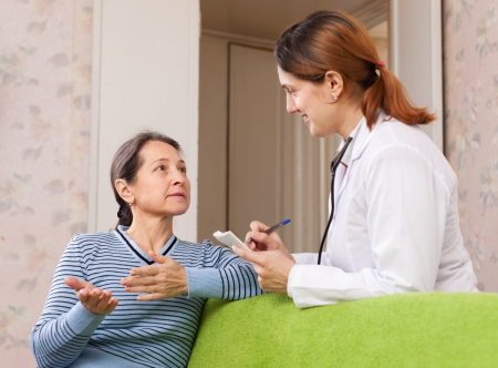 Sick mature woman tells the doctor the symptoms of malaise. Focus on patient Stock Photo - 16682420