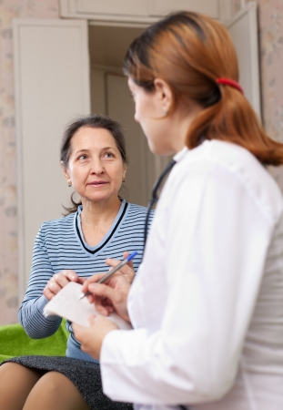 mature woman complaining to doctor about feels at home. Focus on patient Stock Photo - 16682421