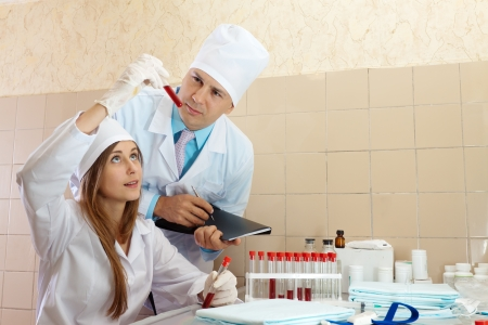 Positive nurse and male doctor with test tube in laboratory Stock Photo - 16709685