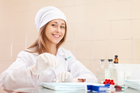 Positive young nurse with syringe in the treatment room photo