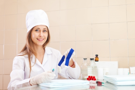 Positive young nurse with tourniquet in medical laboratory photo