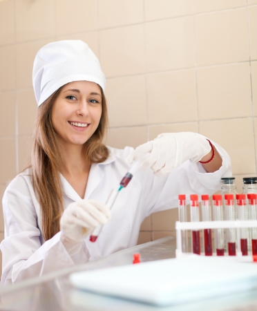 Young nurse works with blood sample in medical laboratory Stock Photo - 16709556