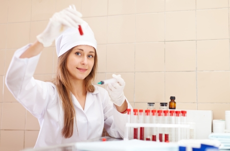 Young nurse works with blood sample in medical laboratory Stock Photo - 16709436