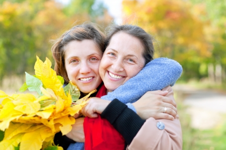 Happy  mature woman with adult daughter in autumn  park Stock Photo - 16753278