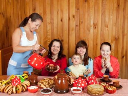 russian ethnicity: Happy family  drinking tea with russian traditional snack