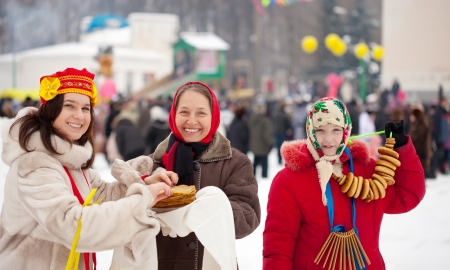 Women eating pancakes during  Shrovetide festival in Russia photo