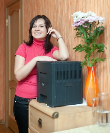 ionizer: Woman  with humidifier in living room Stock Photo