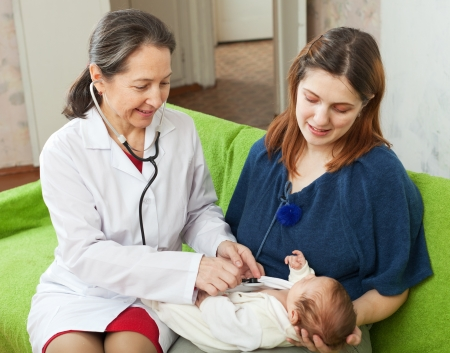 auscultoscope: friendly mature childrens doctor examining newborn baby  with  stethoscope at home Stock Photo
