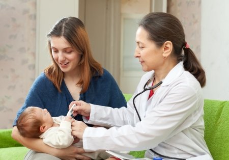 general pediatrician: pediatrician  examining newborn baby with thermometer. Focus on mother Stock Photo