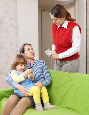 Woman pays nanny for her baby at home Stock Photo - 16791471