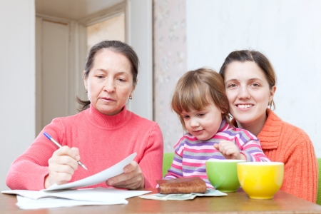 Mature woman and adult daughter with child  fills in payments bills at  home photo