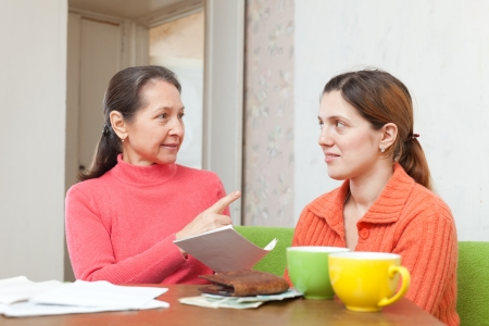 Mature mother and adult daughter is calculates the family budget at  home together photo