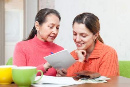 Adult daughter and mother counts the family budget at  home Stock Photo - 16791476