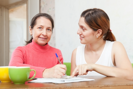 Adult daughter with mother  fills in the questionnaire at  home Stock Photo - 16791467