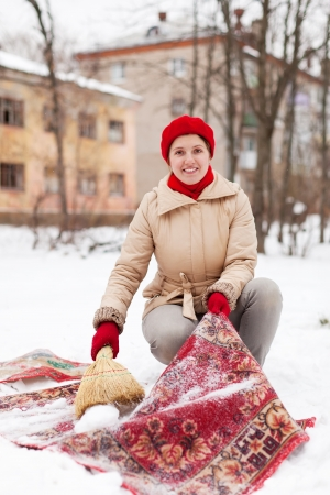 Smiling girl in red cap cleans carpet with snow in winter day outdoor photo