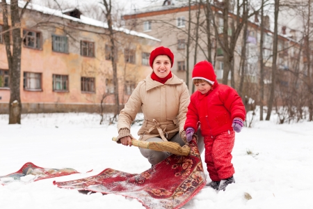 Smiling mother with child cleans rug with snow in winter day outdoor photo