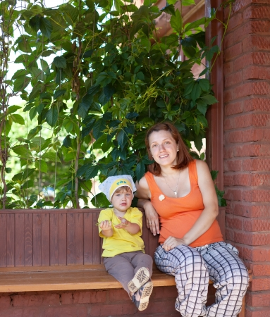 Happy mother and child sits on bench in veranda Stock Photo - 16848577
