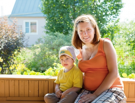 Happy mother and child sits on bench in veranda photo