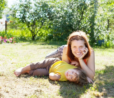 Happy mother and child laying on grass in yard photo