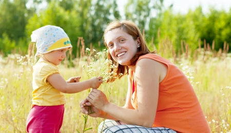 Happy mother with daughter in summer daisy plant Stock Photo - 16848573