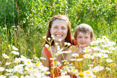 Happy mother with child sits in camomile plant Stock Photo - 16848544