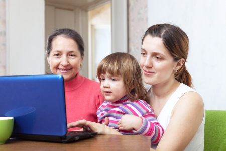 Women of three generations sits on sofa in livingroom with netbook  Stock Photo - 16862941