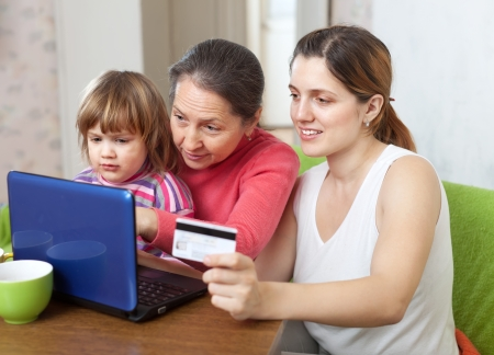 Woman with mother and child shopping online in living room at home photo