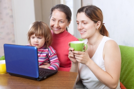 Happy women  of three generations looks the netbook in home interior photo