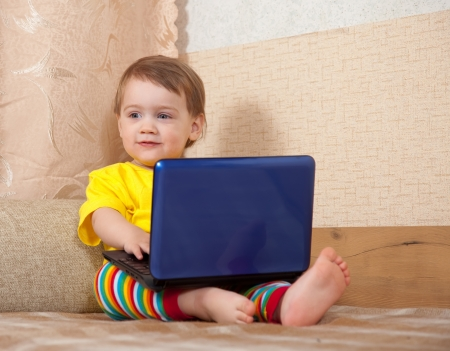 Toddler using laptop on sofa in home Stock Photo - 16862809