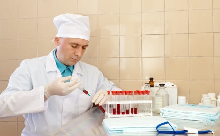 Male doctor with test tube making research in lab photo