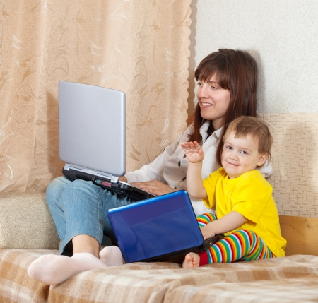 Happy woman and child  sitting on sofa in living room with laptops Stock Photo - 16863520