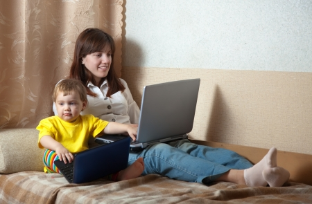 Happy mother and child sitting on the sofa with laptops Stock Photo - 16863260