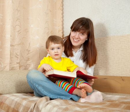 Mother and daughter reading  book together on couch in home Stock Photo - 16863570