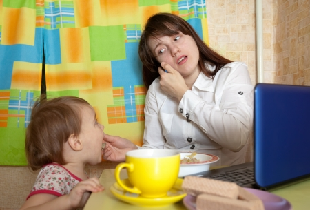businesswoman feeding baby and  speak by mobile at kitchen in morning Stock Photo - 16863435