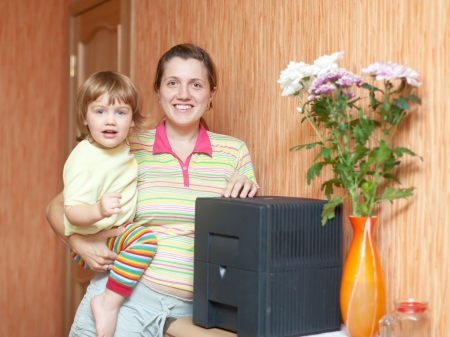 Woman and child uses humidifier at home  photo