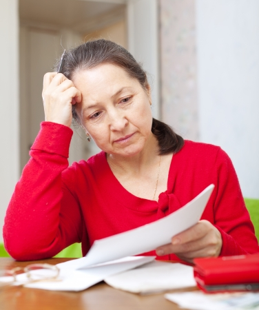 calculated: serious mature woman reads payments  at home Stock Photo