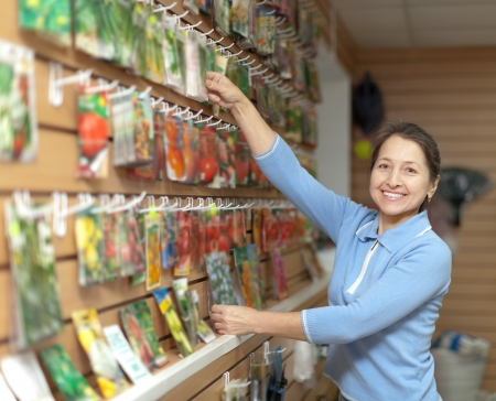 Smiling mature woman chooses packed seeds at store for gardener photo