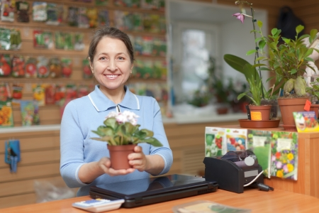 Mature saleswoman with flower at garden store photo