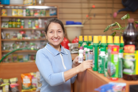 Smiling mature  woman chooses agricultural chemicals in the store for gardeners Stock Photo - 16884464
