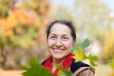 happy seasonable: happy mature woman  in autumn park Stock Photo
