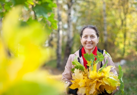 Outdoor portrait of mature woman in autumn with maple posy Stock Photo - 16884465