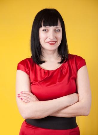 commonplace: Donna in abito rosso su sfondo giallo Archivio Fotografico