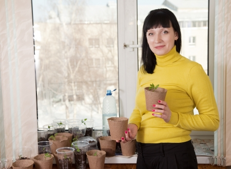 Smiling woman with vaus seedlings at home Stock Photo - 16902096