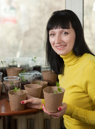 Smiling woman with various seedlings at home Stock Photo - 16902110